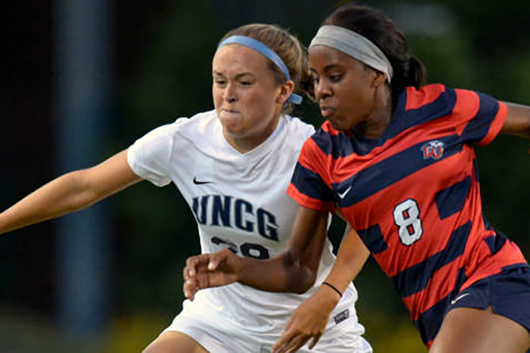 UNCG soccer player battling opponent