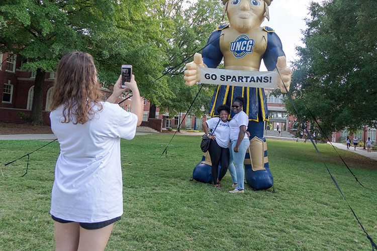 girl taking cellphone photo of Spiro mascot