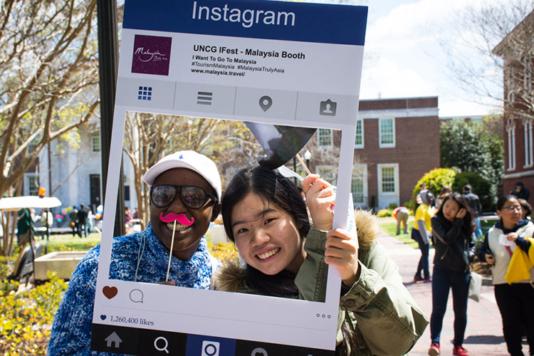 Students pose for picture in an iFest Instagram Frame
